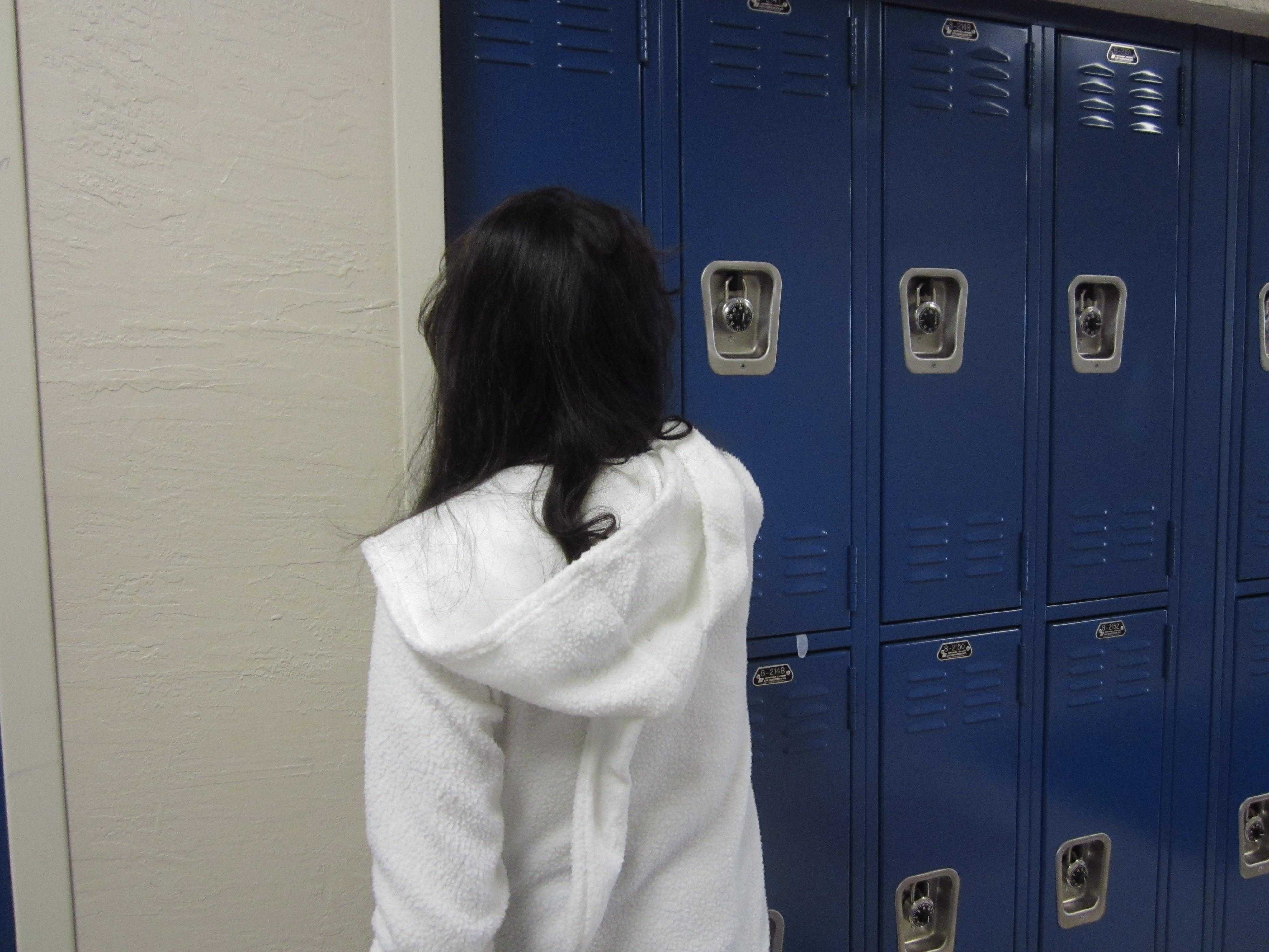 A student rushes to open her locker before the first bell rings.