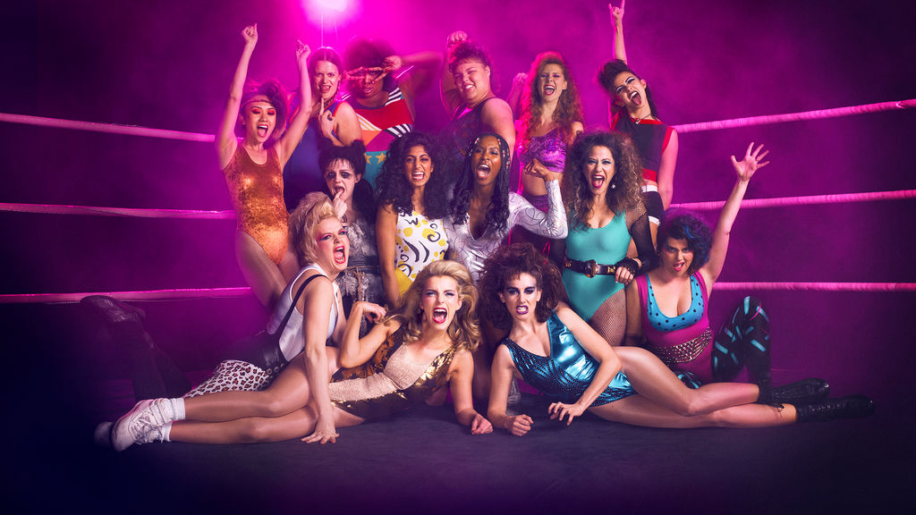 Cast of GLOW poses for the show's Netflix background