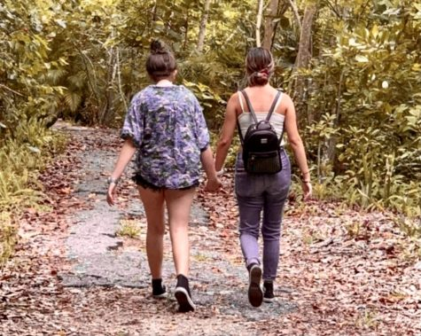 Girlfriends walking side-by-side amongst one another during a nature stroll. They are junior Halina Goldstein (left) and senior Alicia Lewis (right).